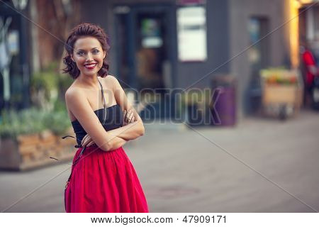 Summer street portrait of a beautiful young Caucasian girl