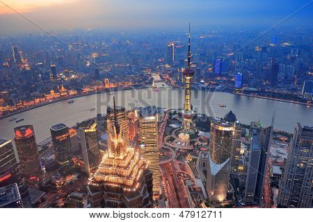 Shanghai aerial view at sunset with urban skyscrapers over river