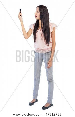 Annoyed woman looking at her cellphone on white background