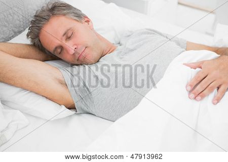 Man sleeping peacefully at home in his bed