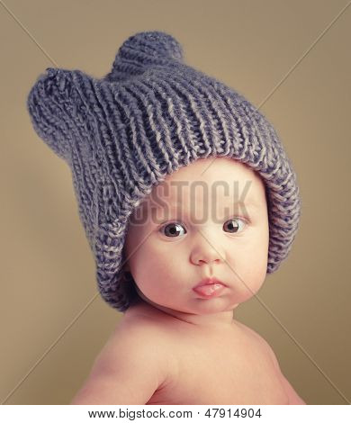 Portrait of cute happy 4 month old baby girl with funny hat