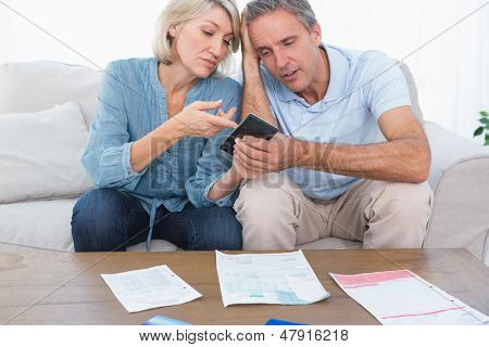 Worried couple going over their debt at home on sofa