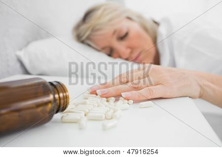 Blonde woman lying motionless after overdosing on tablets at home in bed