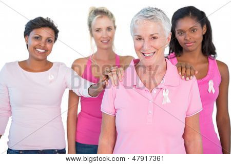 Supportive group of women wearing pink tops and breast cancer ribbons on white background
