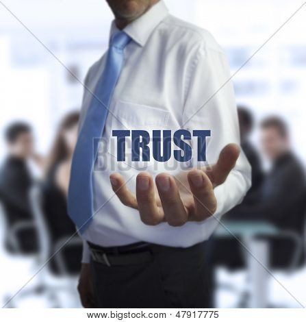 Sophisticated businessman holding the word trust in front of a business team