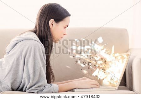 Woman on the couch using laptop with binary codes exploding over