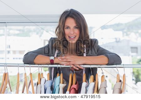 Fashion designer leaning on clothes and smiling to the camera