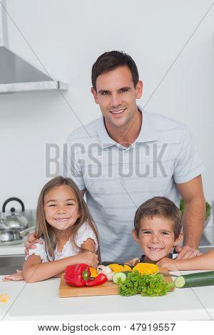 Porträt von einem Vater und seinen Kindern in der Küche, während sie Gemüse vorbereiten