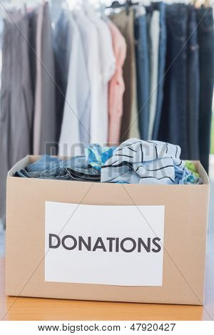 Donations box full of clothes on a table in front of clothes rail