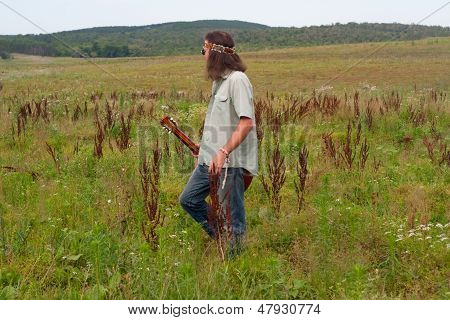 Hippie Musician  With Guitar On The  Meadow