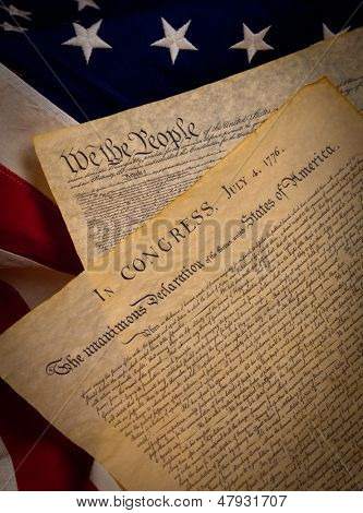 A copy of the constitution and the declaration of independence of the United States on a flag background