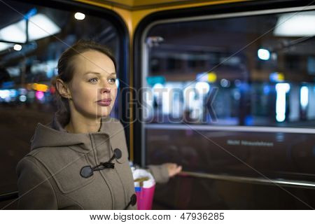 Pretty, young woman on a streetcar/tramway, during her evening commute home from work (color toned image; shallow DOF)