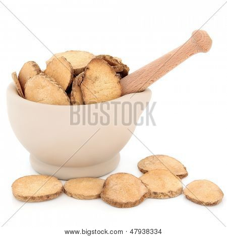 Chinese herbal medicine of water plantain in a stone mortar with pestle over white background.