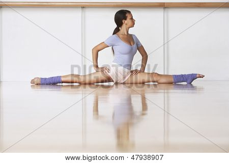 Full length of young ballerina on wooden floor in split position at rehearsal