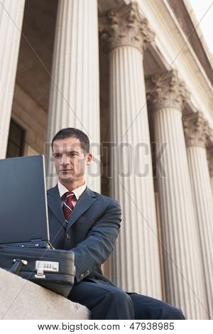 Low angle view of a male lawyer using laptop outside courthouse