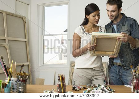 Multiethnic couple looking at canvases in artist studio