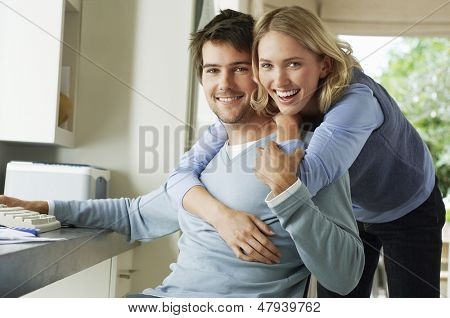 Portrait of a cheerful woman hugging man from behind at home