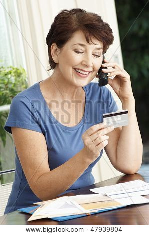 Middle aged woman paying bills through credit card using cellphone