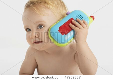 Curious little boy using toy phone isolated on white background
