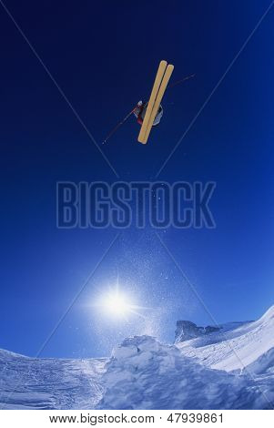Low angle view of skier jumping from mountain cliff against blue sky