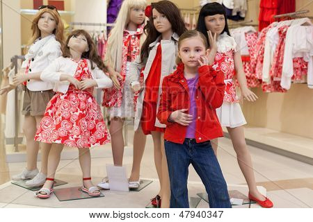 MOSCOW - MAR 18: Jeanette 6 years old trying on clothes together with mannequins in the store children clothes Jakimanka on March 18, 2012 in Moscow, Russia.