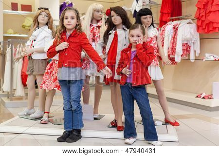 MOSCOW - MAR 18: Anya 7 years old and Jeanette 6 years old trying on red clothes together with mannequins in the store children clothes Jakimanka on March 18, 2012 in Moscow, Russia.