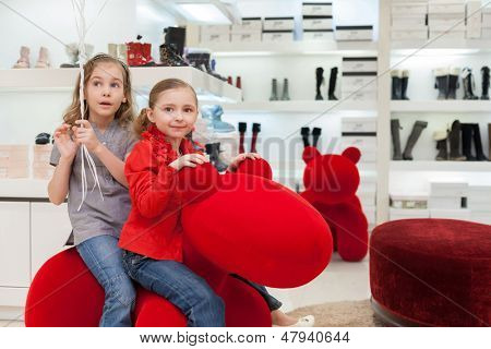 MOSCOW - MAR 18: Anya 7 years old and Jeanette 6 years old having fun in a big red toy at the store children shoes Jakimanka on March 18, 2012 in Moscow, Russia.