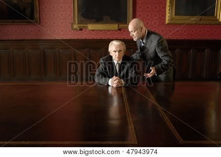 Senior businessman ignoring male colleague in boardroom