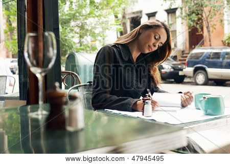 Young woman writing at sidewalk cafe