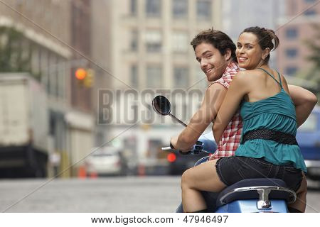 Rear view portrait of a happy couple riding on moped in street