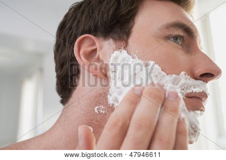 Closeup of a young man applying shaving cream