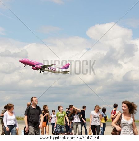 DORTMUND, GERMANY - JUNE 22: Passengers on a runway in airport of Dortmund, Germany on June 22, 2013 under Wizzair plane taking off. Created in 2004, now Wizzair make flights to more than 250 cities
