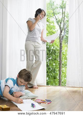 Mother using cellphone while son drawing on the floor