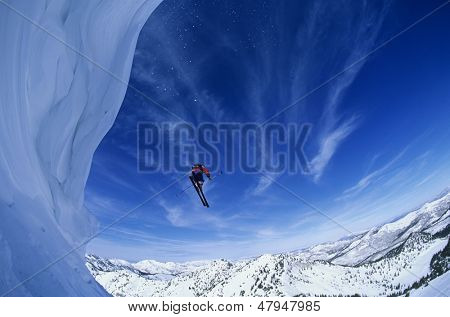 Low angle view of man jumping from mountain ledge against sky