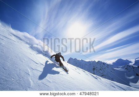 Full length of skier skiing on fresh powder snow