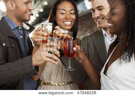 Two happy multiethnic couples toasting drinks at the bar