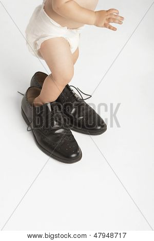 Low section of baby wearing man's shoes isolated on white background