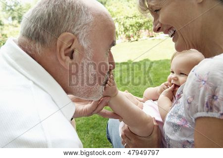 Happy grandparents playing with granddaughter in garden