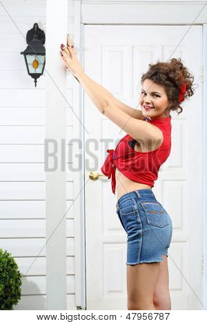 Smiling woman holds pole next to white entrance door of house.