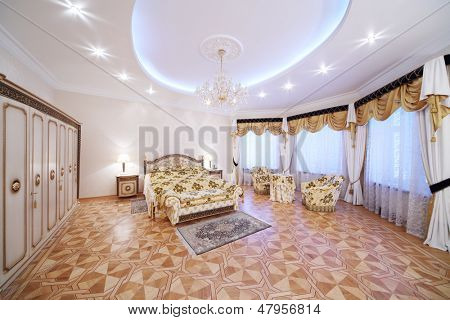 Spacious bedroom with gilt double bed and bedside tables in classic style.