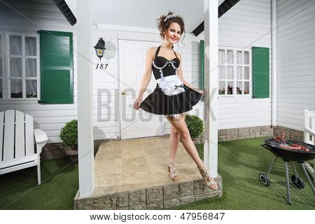 Beautiful housemaid poses near country house and barbecue with sausages.