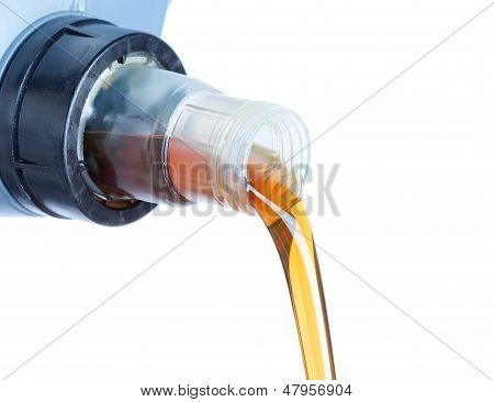 Engine Oil Pouring From A Plastic Canister. On A White Background.