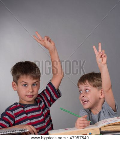enthusiastic schoolboys raising their hands to give an answer, education concept