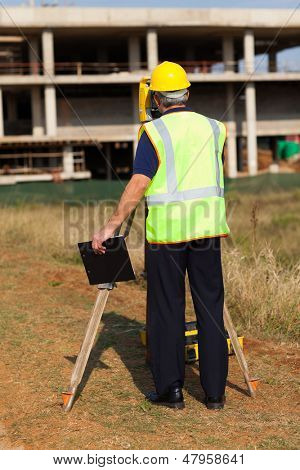 rear view of senior land surveyor working at construction site with theodolite