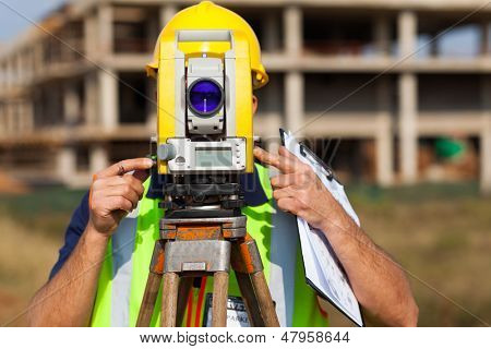 land surveyor looking through theodolite at construction site