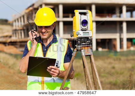 senior land surveyor talking on walkie talkie