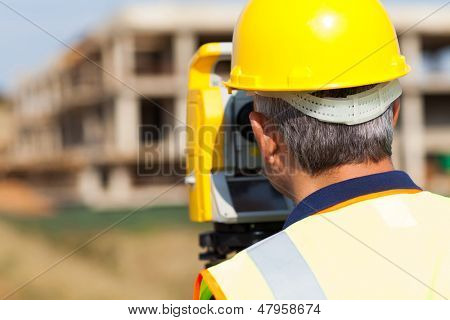 rear view of senior land surveyor working on theodolite