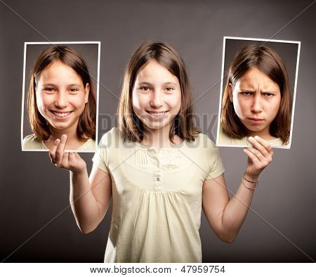 portrait of young girl holding two photos of herself with happy and sad expressions