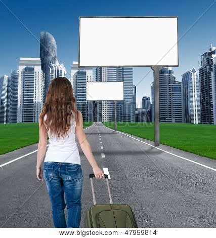 woman walking on the road to the city, in front of an empty Billboards. concept. tourist returns home to the city. moving to the city. billboard on road leading to the city of skyscrapers. back view.