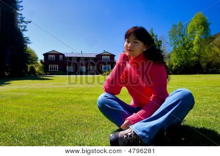 A Girl Sitting On The Meadow
